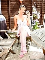 Big breasted blonde in white fishnet hose drinks martini outdoors